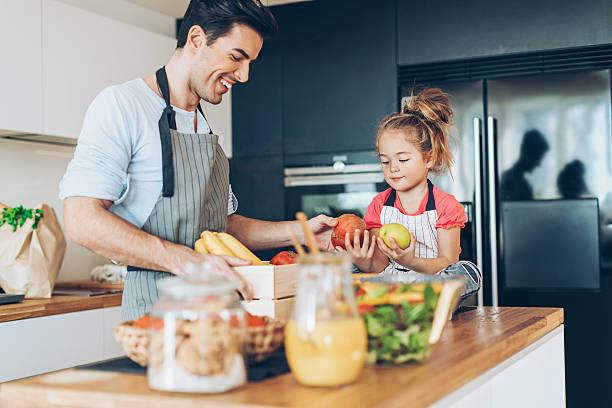 father and daughter sorting fresh fruits - küche aus paletten stock-fotos und bilder