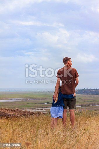 Father and daughter standing on a hill with nature lanscape back view. Little blonde girl with hugging with dad outdoor. Loving child embrace her daddy. Father's Day family greeting card faceless.