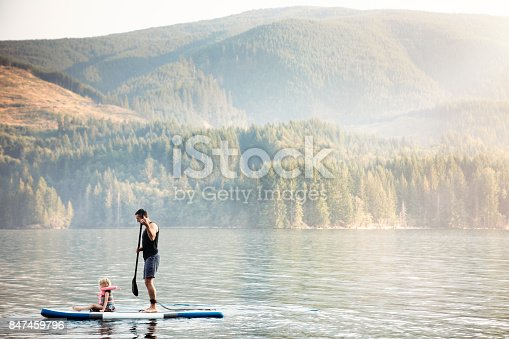 A dad paddles on his SUP, his little girl sitting on the front of the board.  A fun time of bonding and togetherness in a beautiful lake setting.  Shot in Cougar, Washington, USA.
