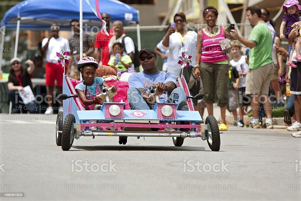Father And Daughter Steer Unique Car In Soap Box Derby royalty-free stock photo