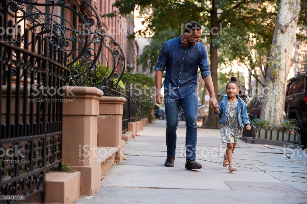 Father and daughter taking a walk down the street stock photo