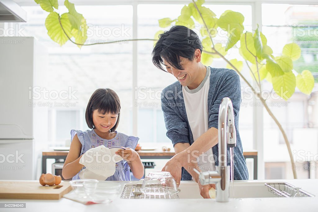 Father and daughter to the dishwashing stock photo