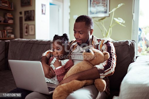 Close up of a father and daughter using a laptop at home in the living room