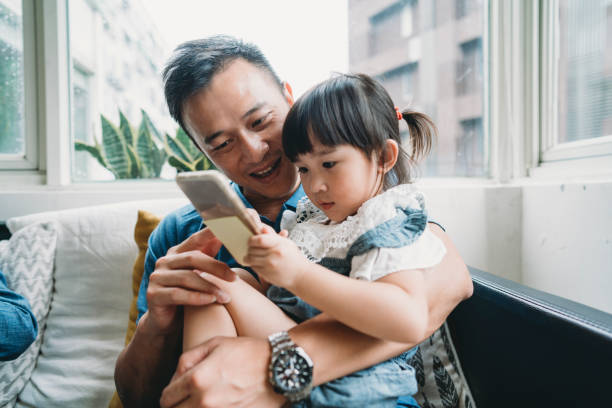 Father and daughter using a mobile phone together sitting on the sofa at home stock photo