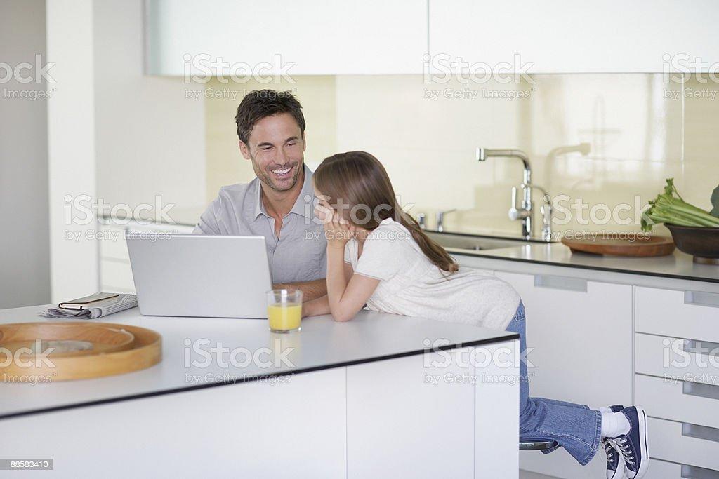 Père et fille à l'aide d'un ordinateur portable dans la cuisine photo libre de droits