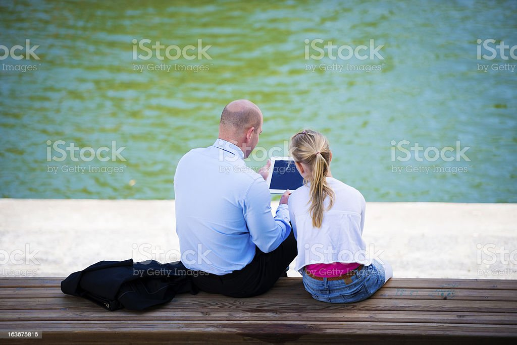 Father and Daughter Using Tablet by the City River royalty-free stock photo