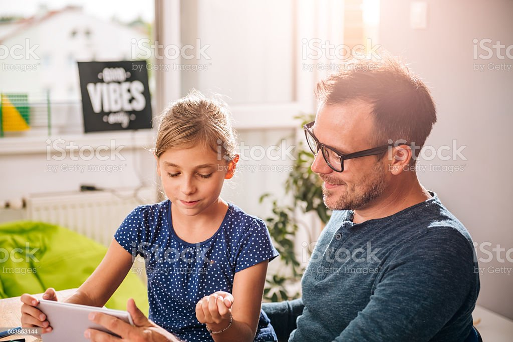 Father and daughter using tablet stock photo