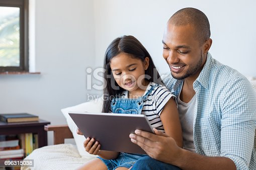 istock Father and daughter using tablet 696315038