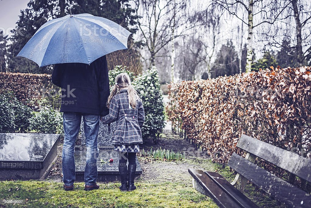 Father and daughter visiting gravestone of deceased mother stock photo