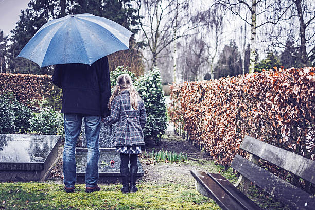 father and daughter visiting gravestone of deceased mother - kerkhof stockfoto's en -beelden