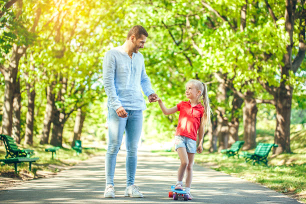 Father and daughter walk outdoors family time stock photo