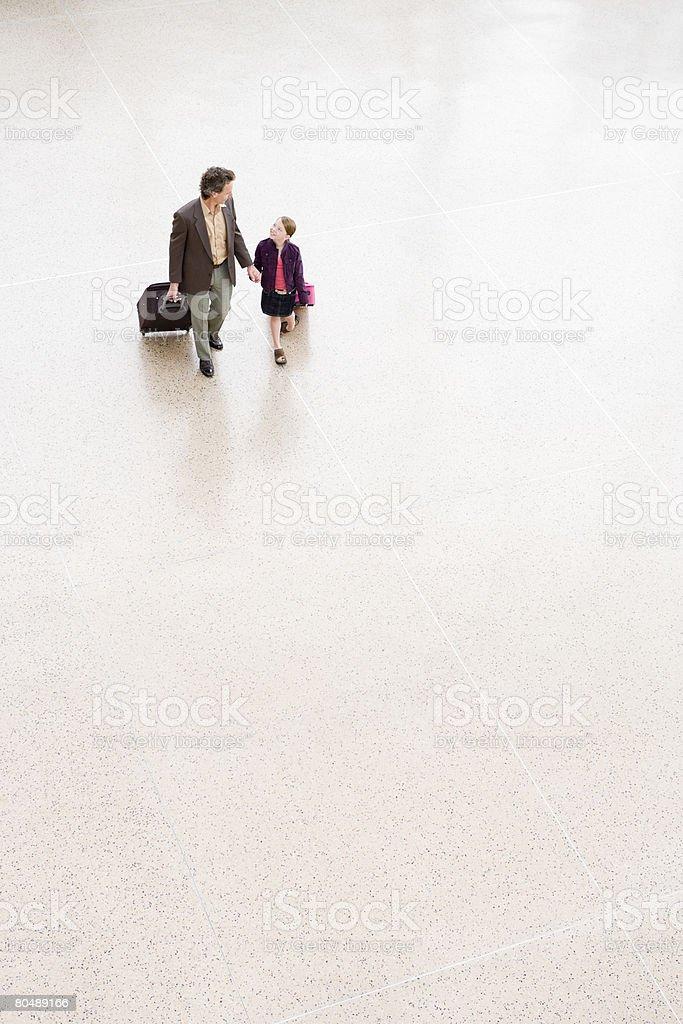 Ein Vater und Tochter zu Fuß auf dem Flughafen Lizenzfreies stock-foto
