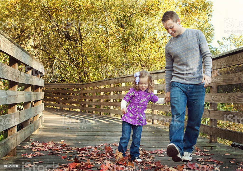 Father and daughter walking together outdoors royalty-free stock photo