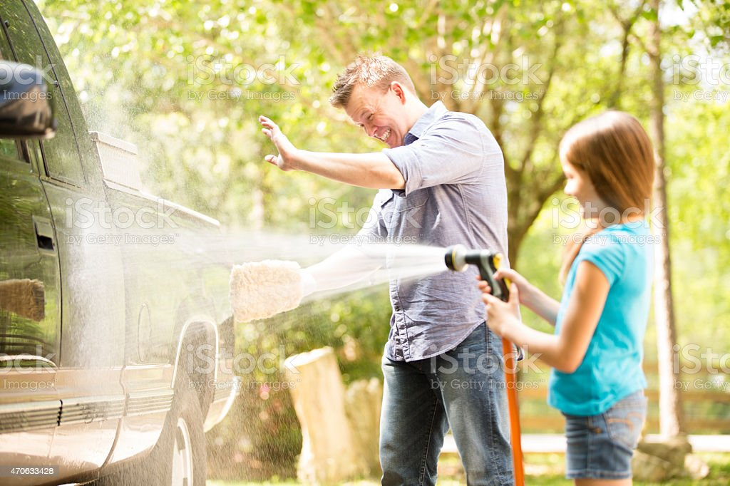 Père et fille laver le véhicule de famille ensemble à l'extérieur. - Photo