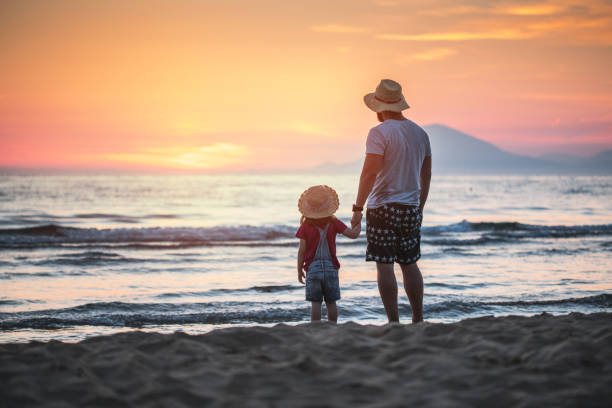 Father and daughter watching sunset at sea stock photo