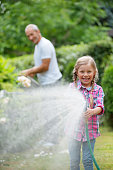Father and daughter watering plants in garden