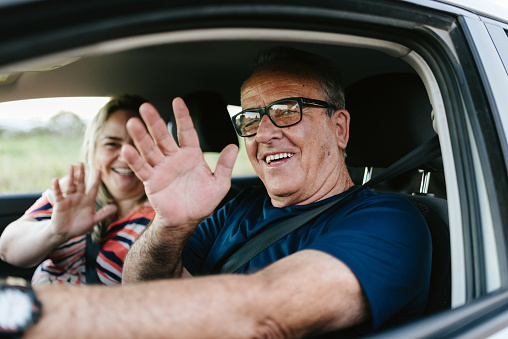 Father and daughter waving in the car
