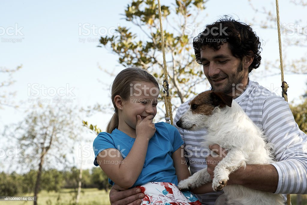 Father and daughter (8-9) with dog in garden royalty-free stock photo