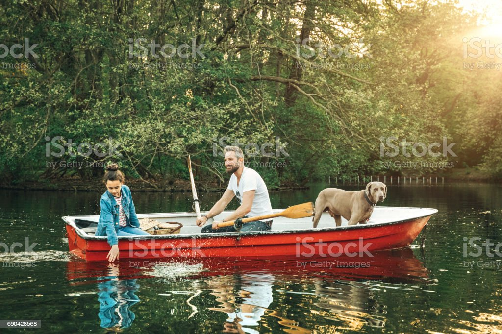 Father and daughter with dog in rowboat on lake – Foto