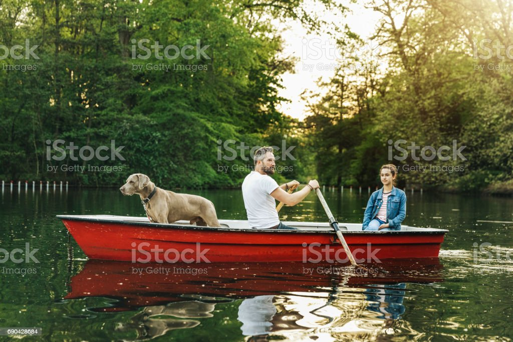 Father and daughter with dog in rowboat on lake stock photo