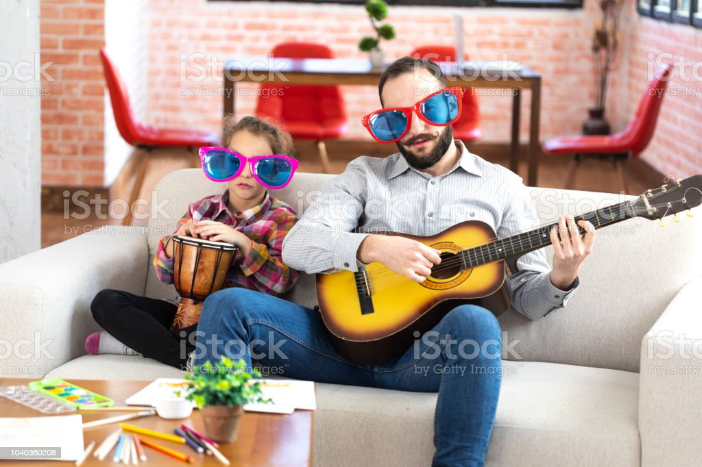 Father And Daughter With Funny Sunglasses Playing Music