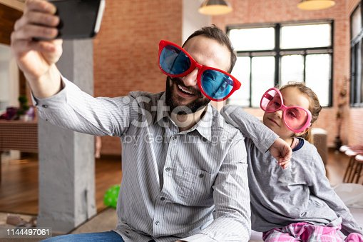 Father and daughter with funny sunglasses taking selfie at home.