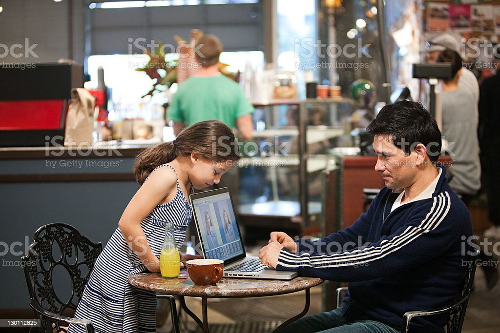 Father and daughter with laptop in cafe stock photo