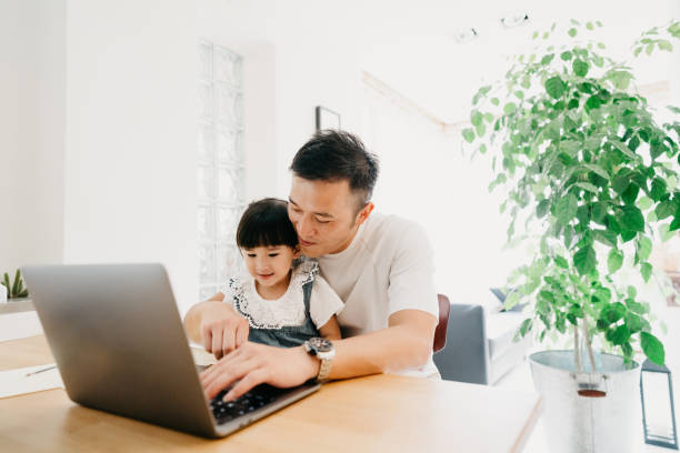 Father and daughter working together at home - The girl is following an online school lesson stock photo
