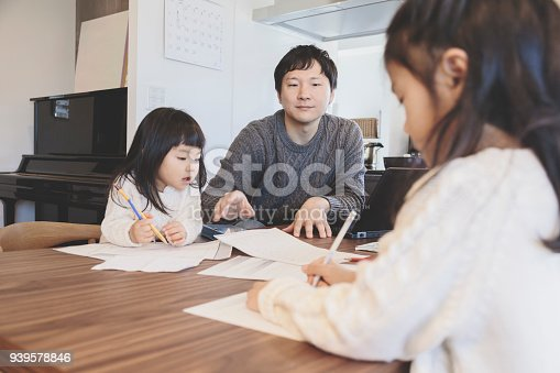 1152545468 istock photo Father and daughters at home 939578846