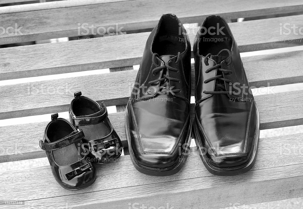 Father and daughter's black shiny shoes stock photo