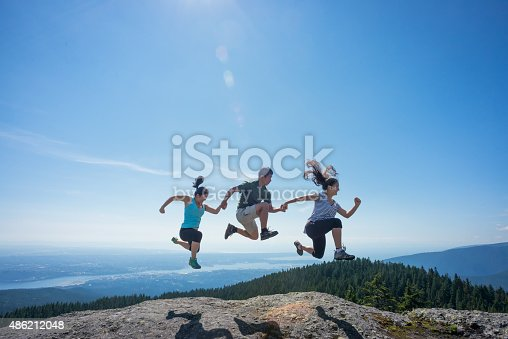 903015102 istock photo Father and Daughters Jumping on Mountain Top, Holding Hands 486212048