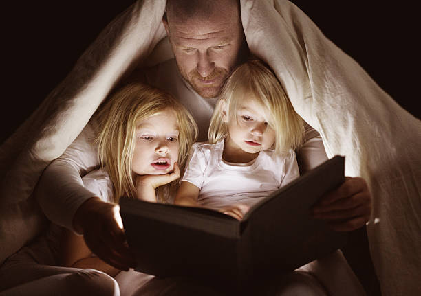 father and daughters reading book at bedtime - fairy tale stock pictures, royalty-free photos & images