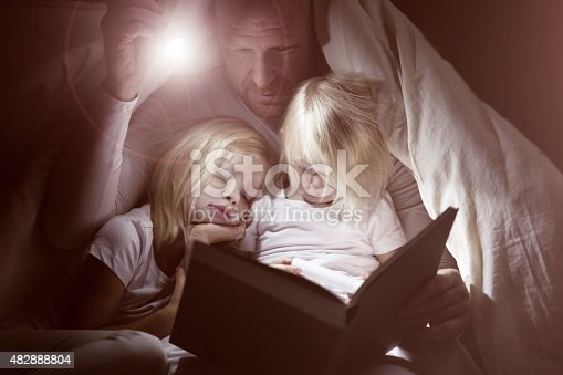 Shaved middle aged father and young blonde daughters reading a book at bedtime by the light of a torch