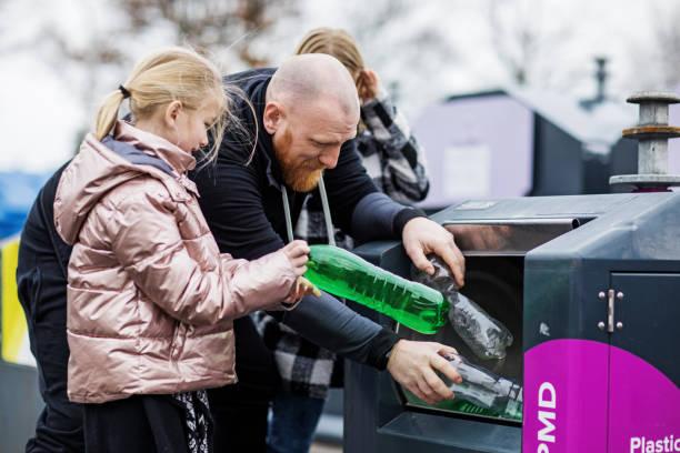 Vater und Töchter recyceln Plastikflaschen – Foto