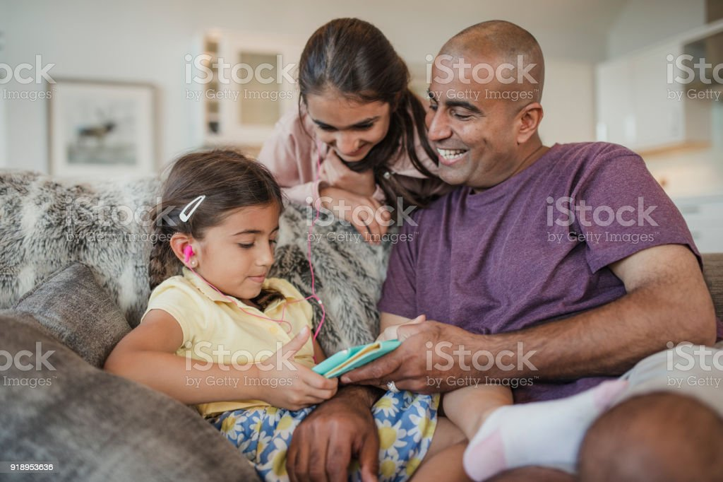 Father and Daughters Using a Digital Tablet stock photo