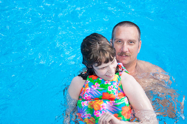 Father and disabled daughter bonding in pool stock photo