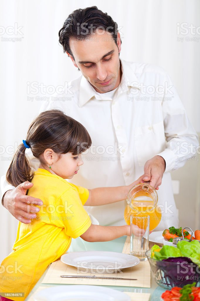 Father and doughter pouring orange juice into glass royalty-free stock photo