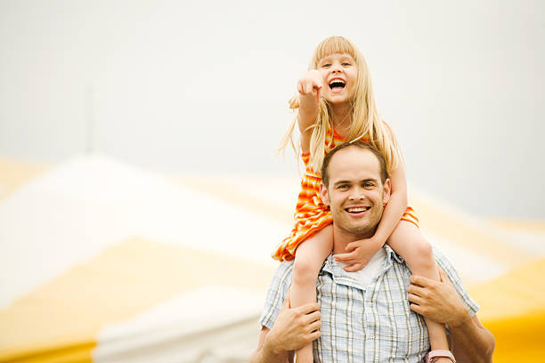 Father and Girl Child on Shoulders at Fair or Circus stock photo