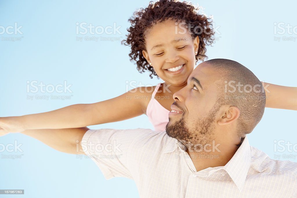 Father and girl enjoying a flight against blue sky royalty-free stock photo