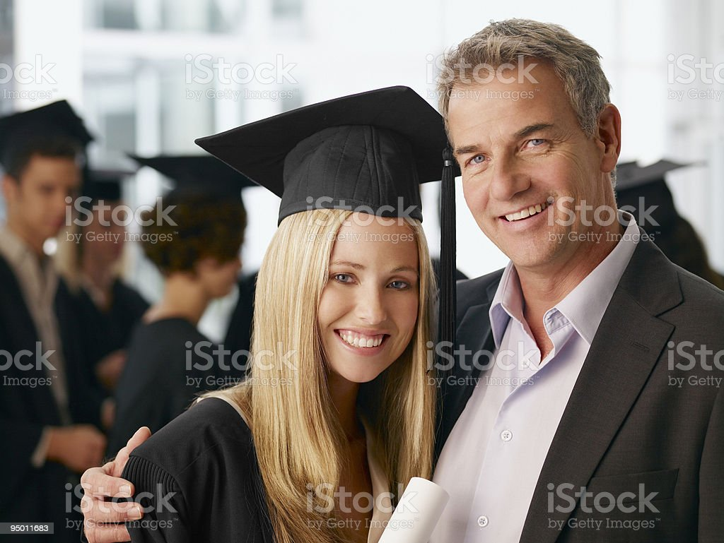 Father and graduate daughter hugging stock photo