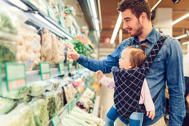 Pai e sua filha bebê de compras de supermercado. - foto de acervo