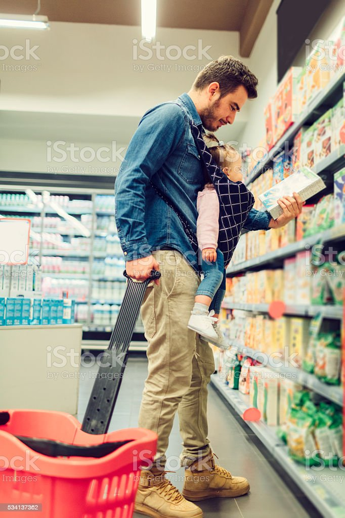 Father And His Baby Daughter Shopping In Local Supermarket. stock photo