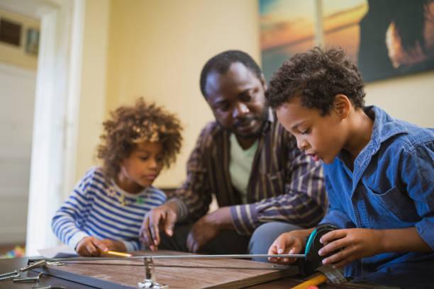 Vater und seine Kinder machen einige DIY-Arbeit zu Hause – Foto
