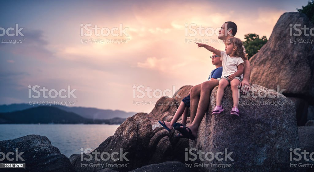 Father and his children watching the sunset over sea stock photo