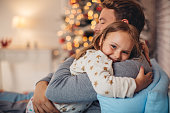 Father and his cute daughter in front of christmas tree, lying on bed. Girl embracing daddy.