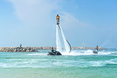 istock Father and his daughter posing at new flyboard at Caribbean tropical beach. Positive human emotions, feelings, joy. Funny cute child making vacations and enjoying summer. 1014418836