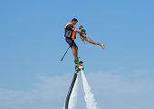 istock Father and his daughter posing at new flyboard at Caribbean tropical beach. Positive human emotions, feelings, joy. Funny cute child making vacations and enjoying summer. 885367596