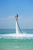 istock Father and his daughter posing at new flyboard at Caribbean tropical beach. Positive human emotions, feelings, joy. Funny cute child making vacations and enjoying summer. 895278192