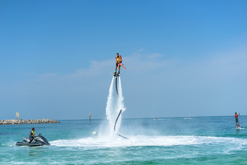 istock Father and his daughter posing at new flyboard at Caribbean tropical beach. Positive human emotions, feelings, joy. Funny cute child making vacations and enjoying summer. 899264438