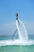 istock Father and his daughter posing at new flyboard at Caribbean tropical beach. Positive human emotions, feelings, joy. Funny cute child making vacations and enjoying summer. 962077998